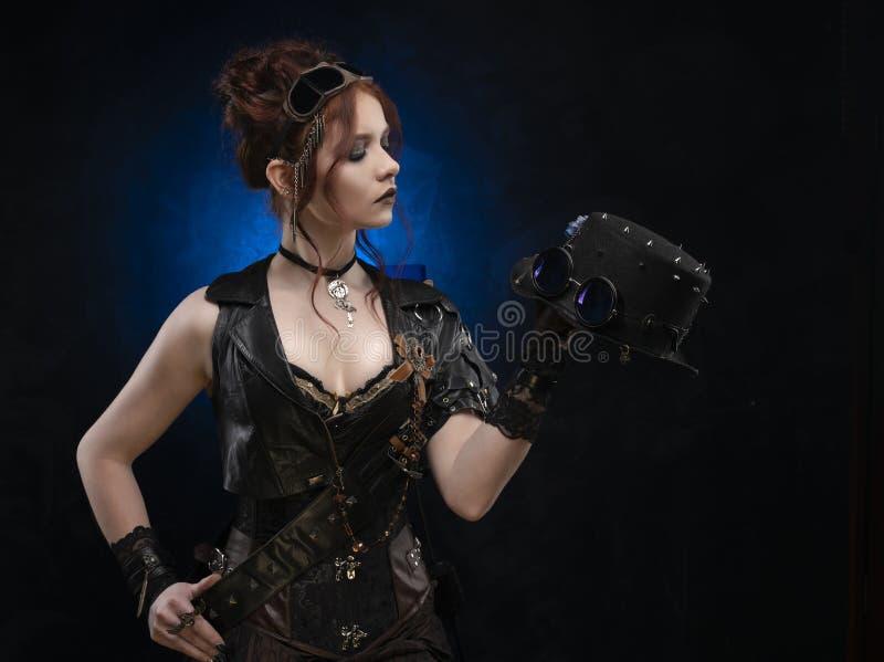 Belle fille rousse de cosplayer portant un corset de style victorien de steampunk et un gilet en cuir, avec de grands seins dans  image stock