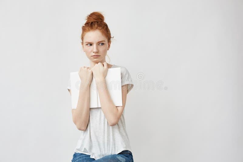 Belle fille rousse effrayée tenant le livre regardant dans le côté photographie stock libre de droits