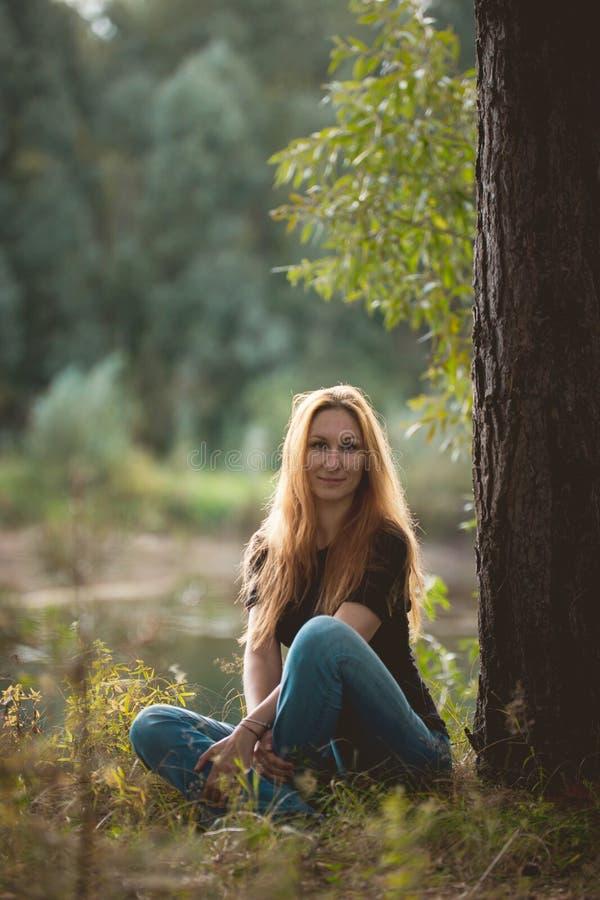 Belle fille rousse s'asseyant près de la rivière à la forêt et regardant à l'appareil-photo photos libres de droits