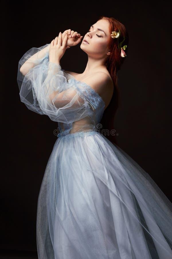 Belle fille rousse sexy avec de longs cheveux dans le coton de robe rétro Verticale de femme sur le fond noir Yeux profonds Beaut photos libres de droits