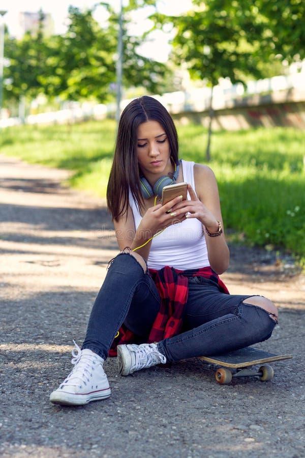 Belle fille s'asseyant ? la planche ? roulettes et au t?l?phone portable d'utilisation image stock