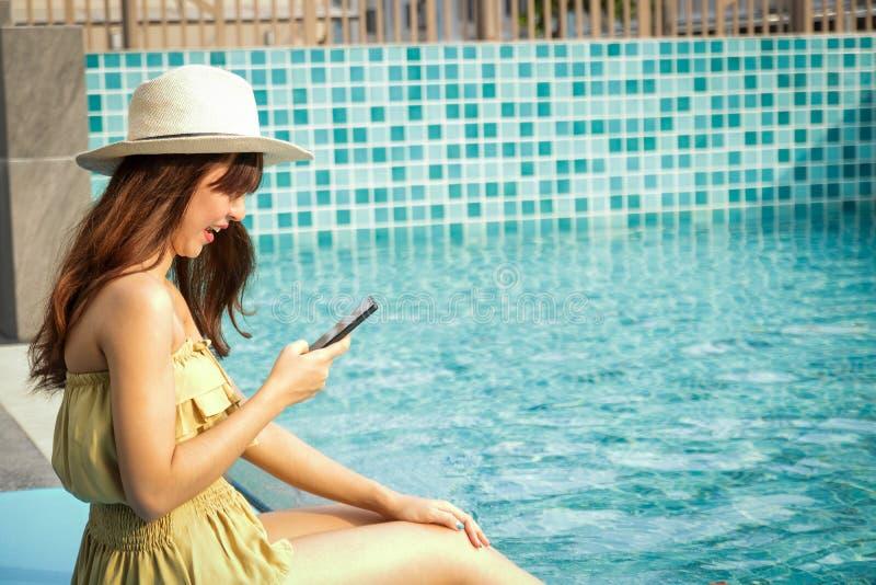 Belle fille s'asseyant au téléphone à la piscine photo stock
