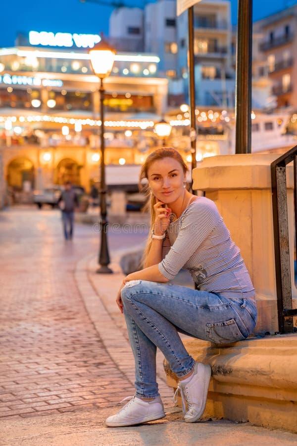 Belle fille s'asseyant par les Doc.s dans le temps de soirée photo stock