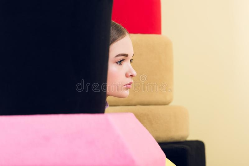 belle fille s'asseyant près du grands vernis à ongles et rouge à lèvres photos stock