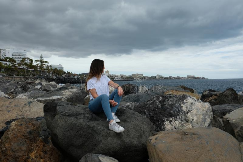 Belle fille s'asseyant sur des roches de plage regardant à la mer photos libres de droits