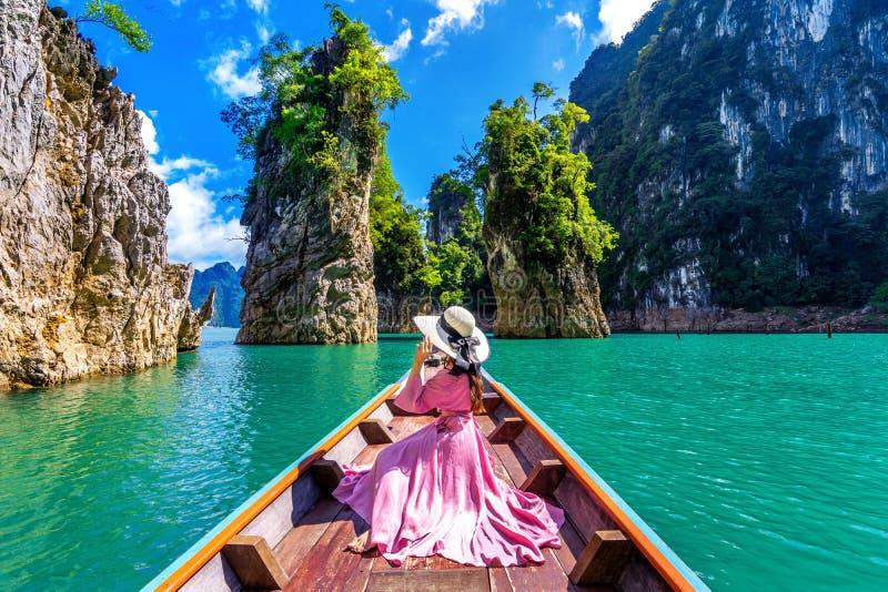 Belle fille s'asseyant sur le bateau et regardant aux montagnes dans le barrage de Ratchaprapha photographie stock