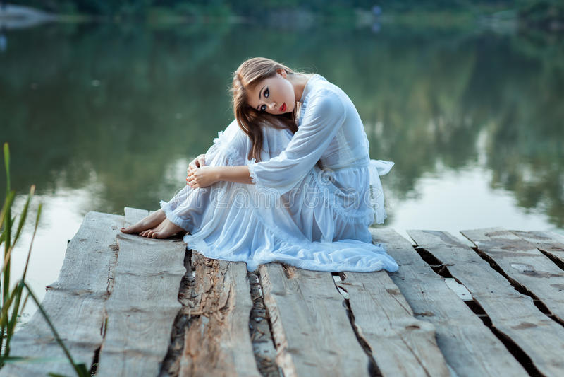 Belle fille s'asseyant sur le quai ennuyé image libre de droits