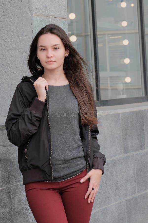 Belle fille s?rieuse regardant l'appareil-photo Veste noire de style à la mode moderne, jeans rouges, chemisier gris Promenades e photos libres de droits