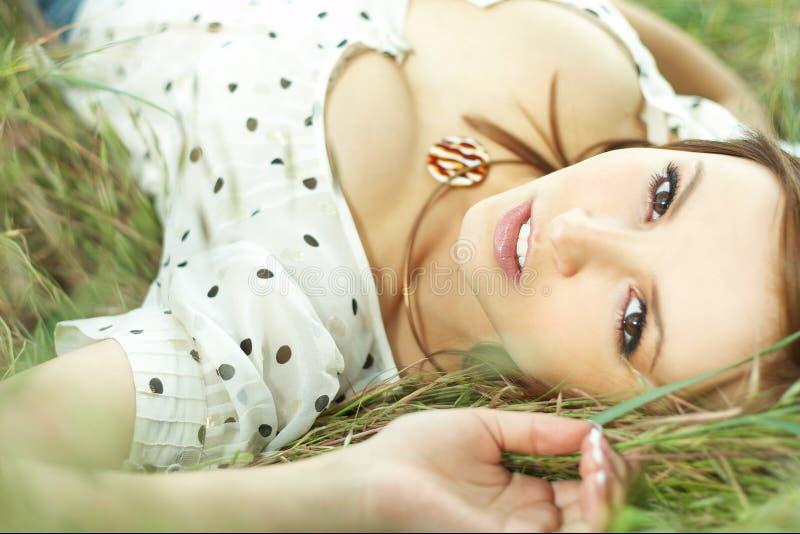 Belle fille se couchant de l'herbe photographie stock