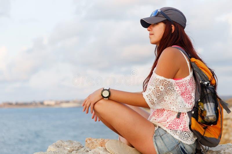 Belle fille se reposant sur la mer calme en pierre et regardante image libre de droits