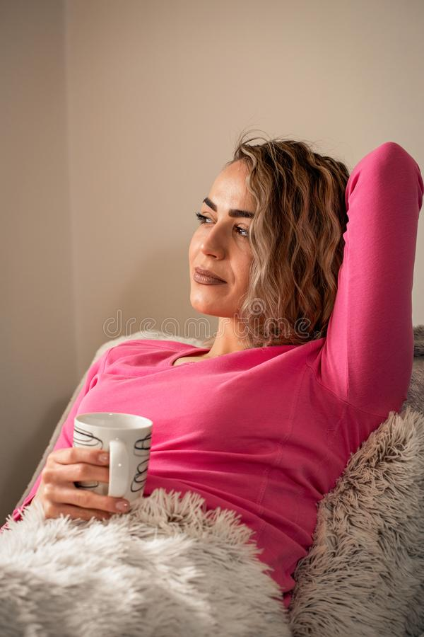 Belle fille se situant dans le lit et appréciant en café à la maison photos stock