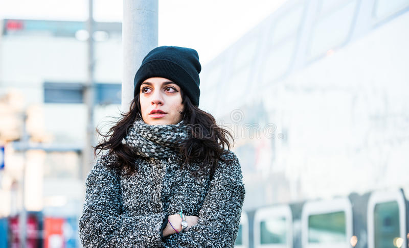 Belle fille se tenant près de la gare ferroviaire la jugeant à l'obstacle larmes - vue franche étroite photo libre de droits