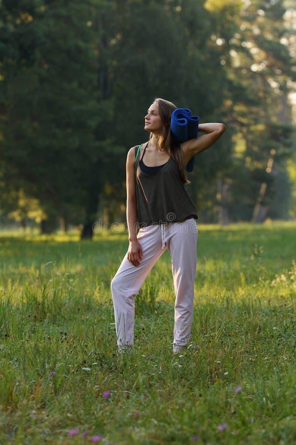 Belle fille semblant partie et tenant le tapis de yoga en parc photos libres de droits