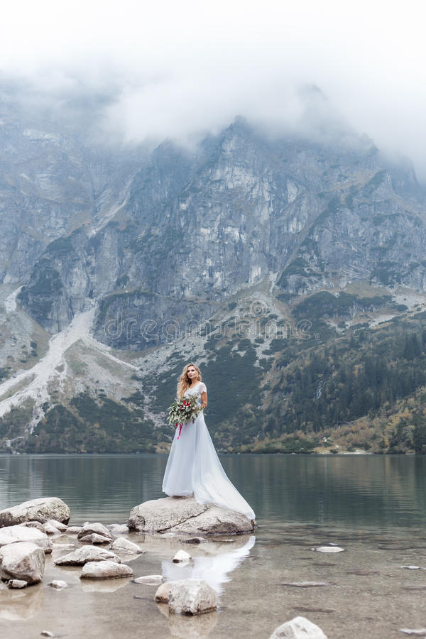 Belle fille sensible dans la robe de mariage bleue de jeune mariée d'air avec les boucles luxueuses dans les montagnes près du la photos stock