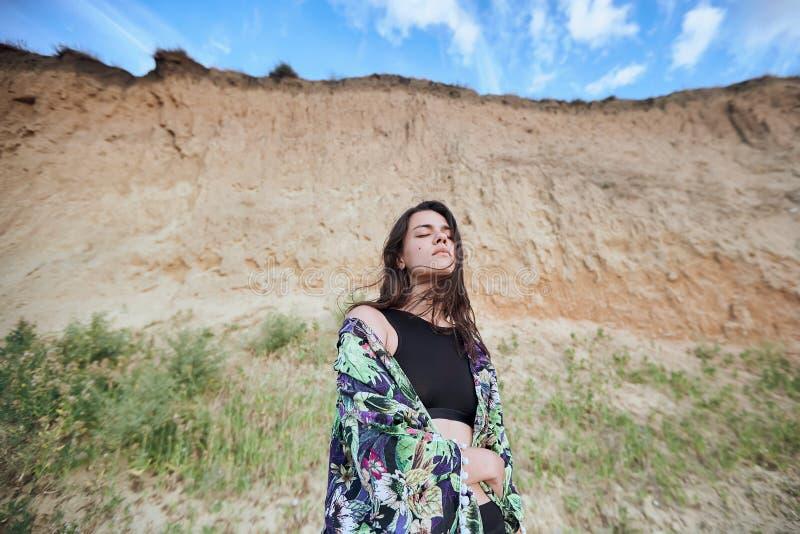 Belle fille sensuelle posant près de la roche sur la plage sablonneuse Jeune femme bronz?e des vacances d'?t photos stock