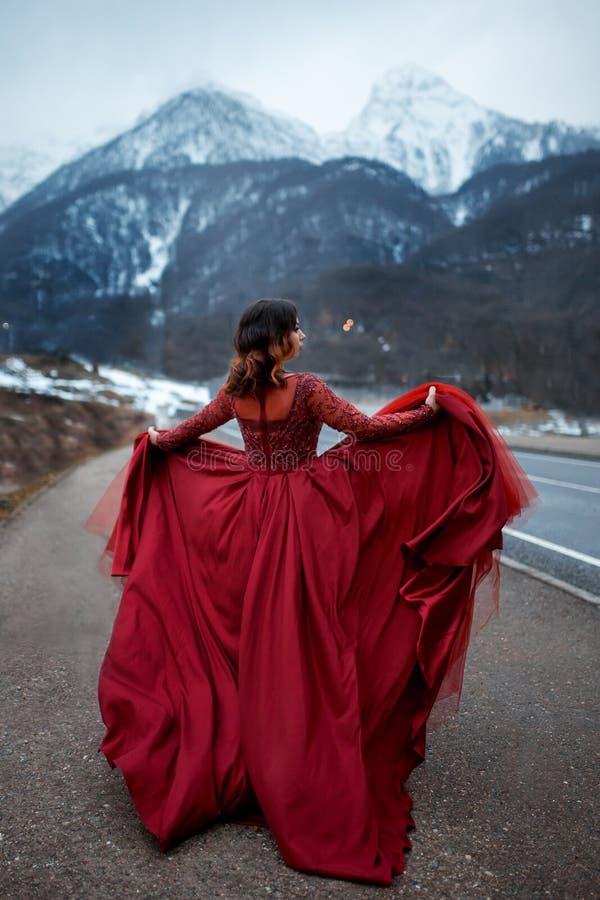 Belle fille sexy élégante dans la grande robe fraîche rouge sur la route, en montagnes image libre de droits
