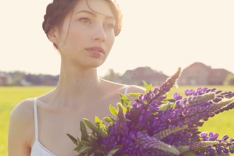 Belle fille sexy avec les fleurs de loup douces avec de beaux cheveux dans un bain de soleil blanc se tenant dans un domaine au c image libre de droits