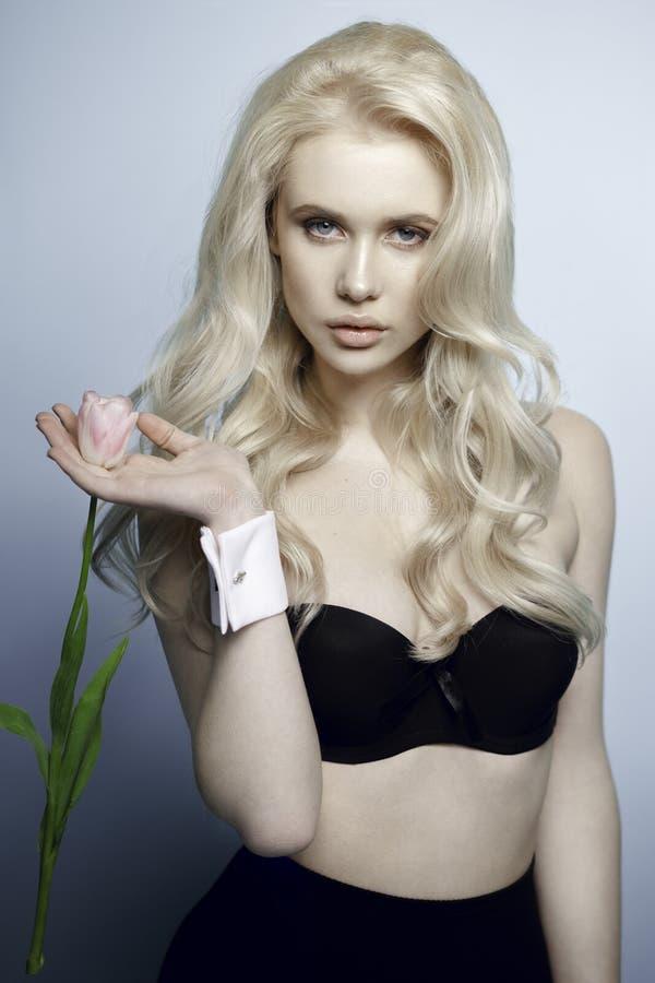 Belle fille sexy blonde dans un sous-vêtement noir, tenant une tulipe, regardant la caméra, sur un fond blanc images libres de droits