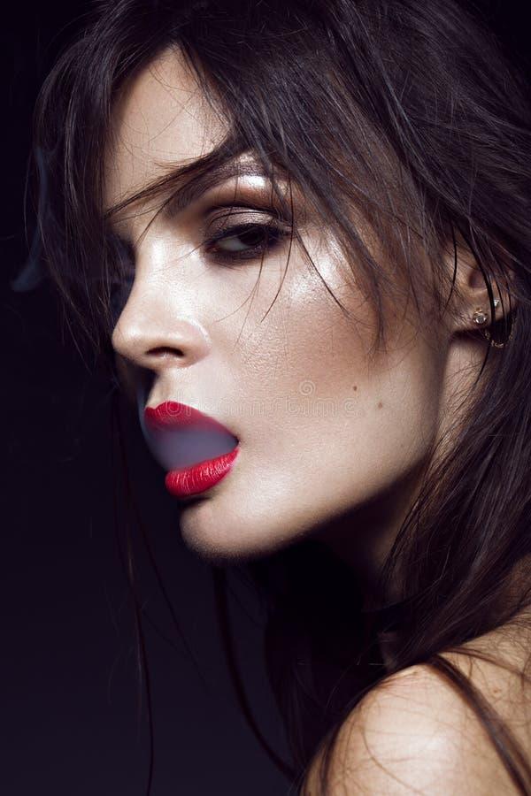 Belle fille sexy de brune avec le maquillage lumineux, lèvres rouges, fumée de bouche Visage de beauté images stock