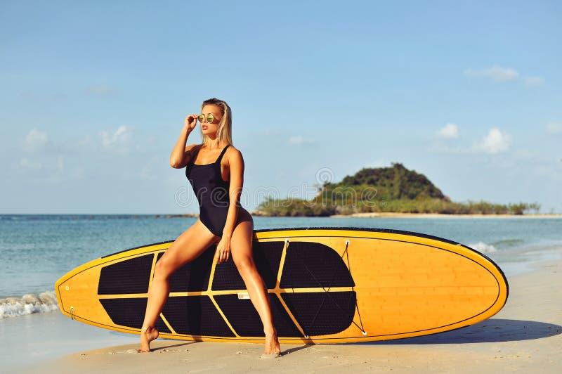 Belle fille sexy de surfer de jeune femme dans le bikini avec le ressac blanc photo libre de droits