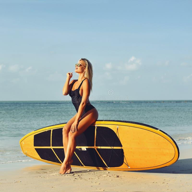 Belle fille sexy de surfer sur une plage image libre de droits