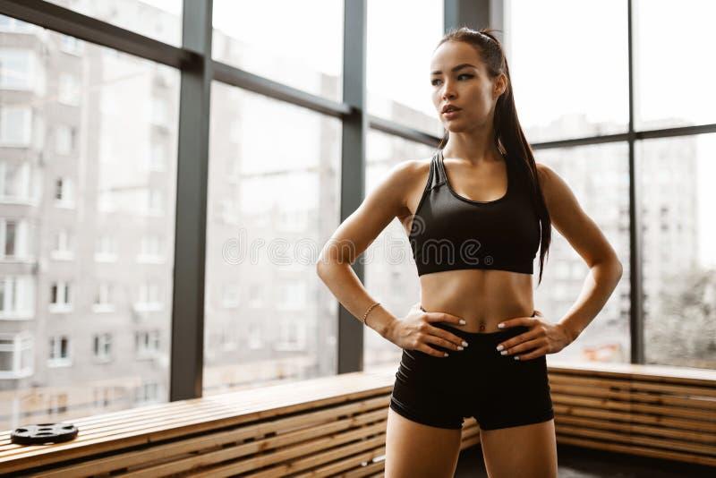 Belle fille sportive avec les cheveux bruns habill?s dans le dessus de sports et les supports noirs de shorts dans le gymnase photos stock