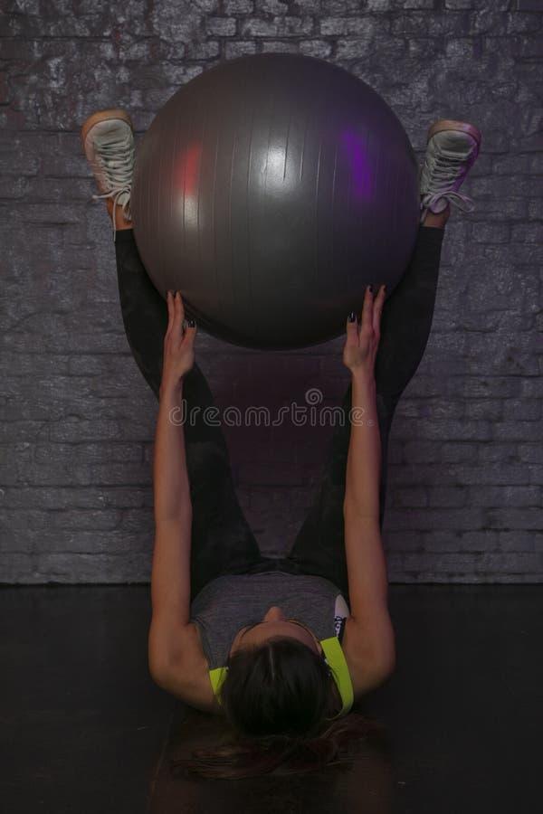 Belle fille sportive pratiquant avec une boule au gymnase, jolie silhouette photos libres de droits
