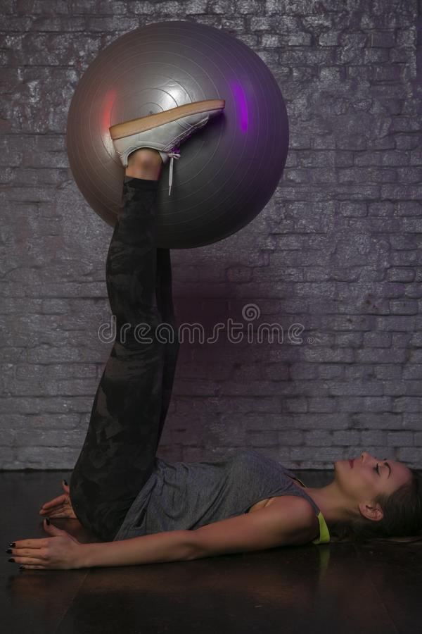 Belle fille sportive pratiquant avec une boule au gymnase, jolie silhouette image stock