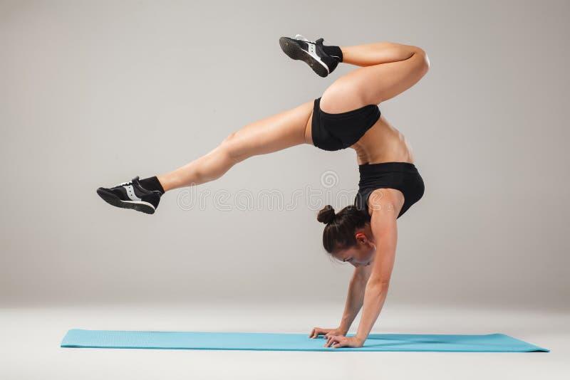 Belle fille sportive se tenant dans la pose d'acrobate ou l'asana de yoga images libres de droits