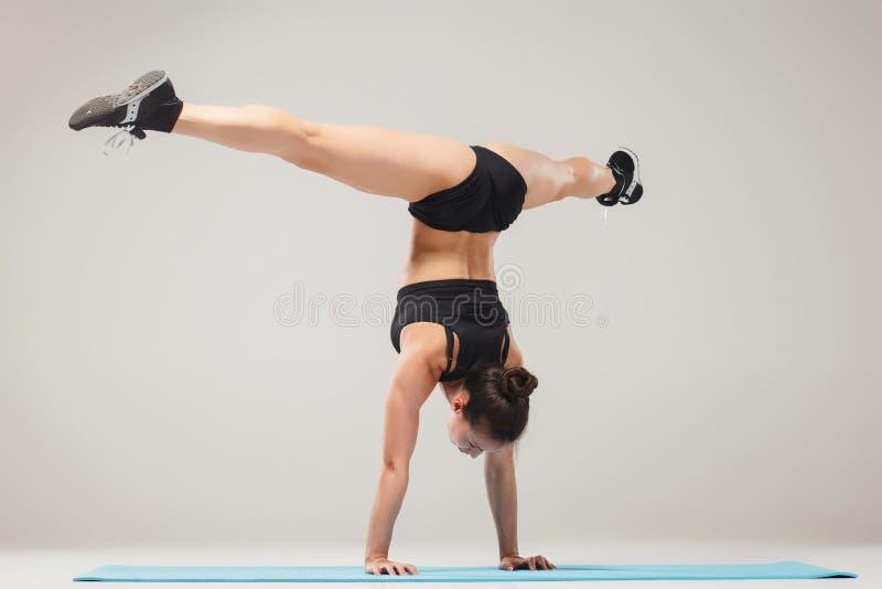 Belle fille sportive se tenant dans la pose d'acrobate ou l'asana de yoga photographie stock