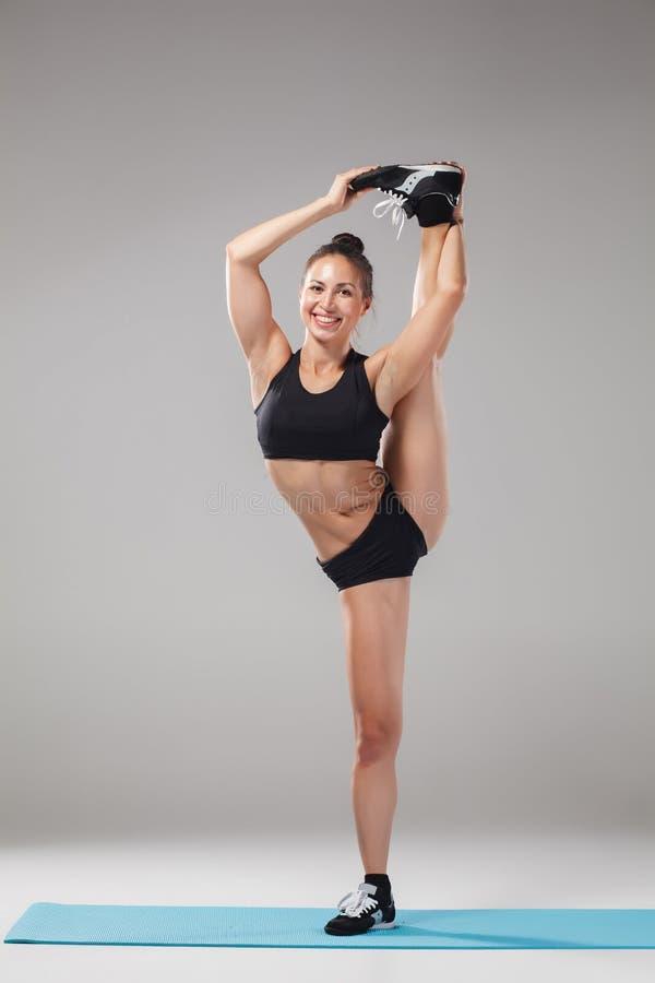 Belle fille sportive se tenant dans la pose d'acrobate ou l'asana de yoga photos stock