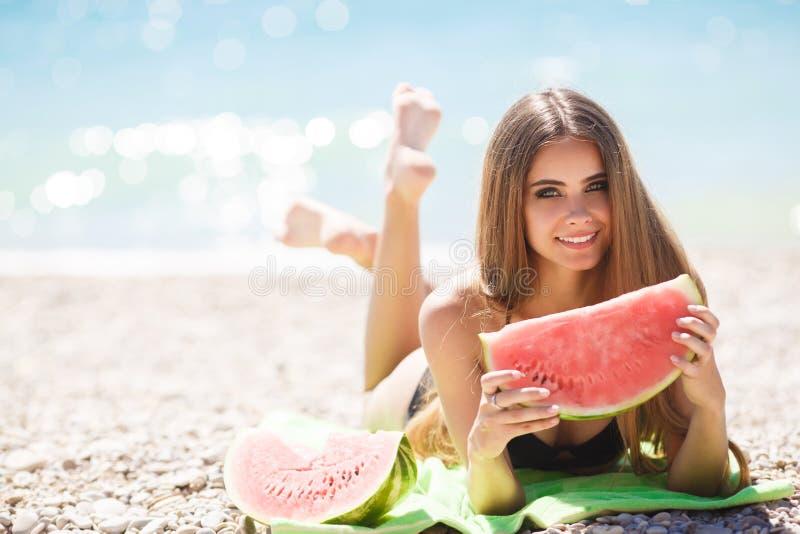 Belle fille sur la plage mangeant la pastèque photo stock