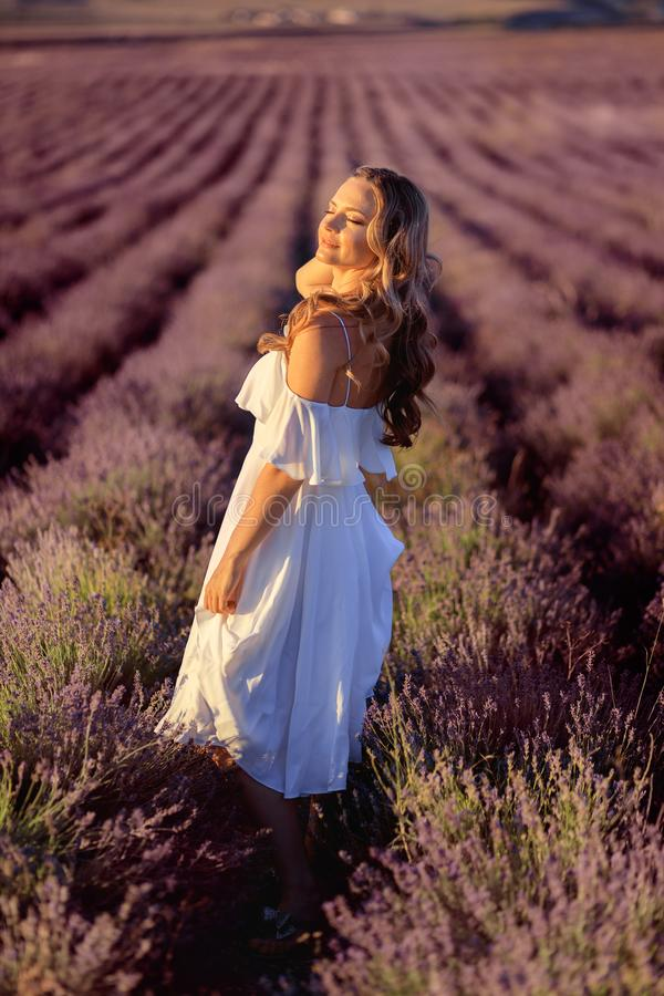 Belle fille sur le gisement de lavande Belle femme dans le domaine de lavande sur le coucher du soleil images libres de droits