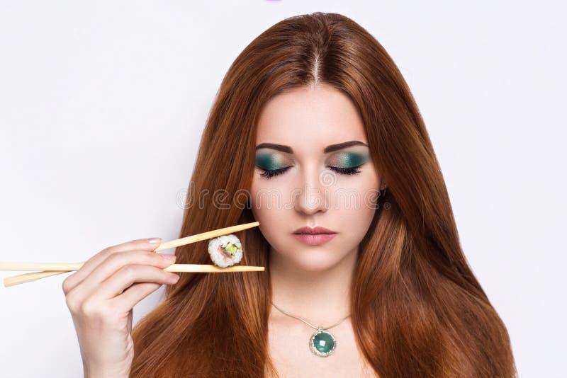 Belle fille tenant des sushi Rolls photographie stock