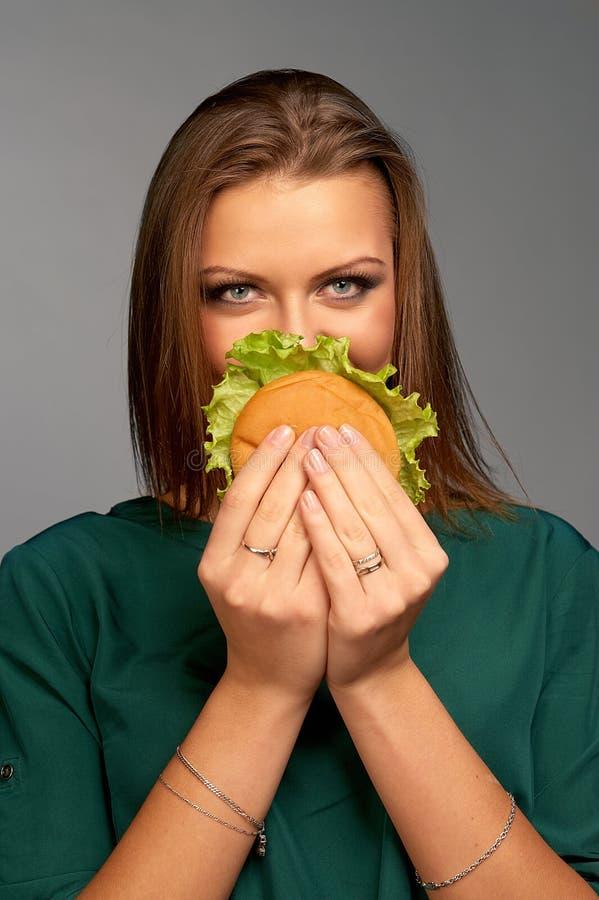 Belle fille tenant l'hamburger image stock