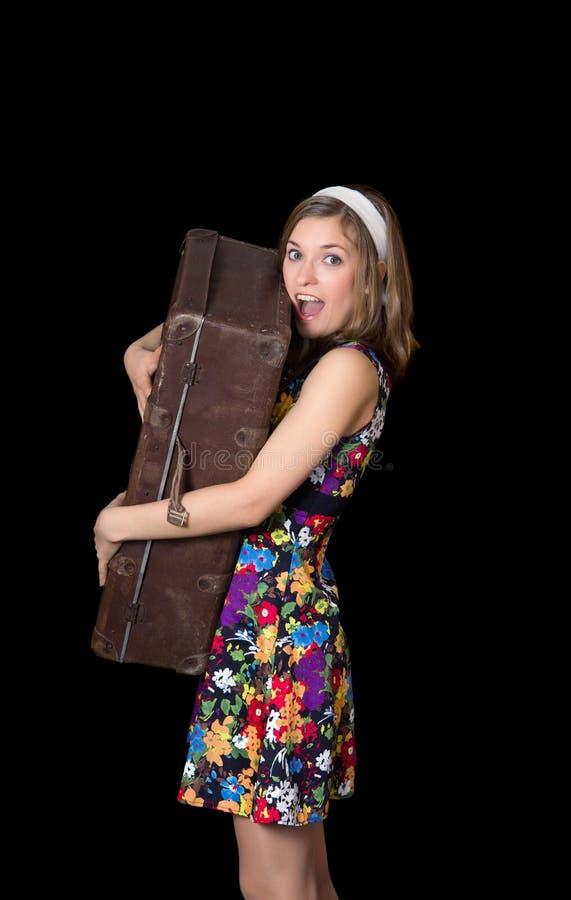 Belle fille tenant la vieille valise et des cris photographie stock