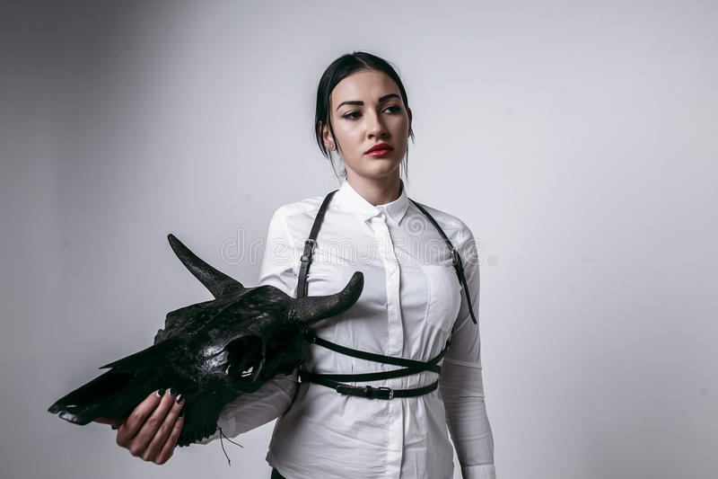 Belle fille tenant le crâne de vache dans la ceinture blanche de chemise et d'épée d'isolement photo libre de droits