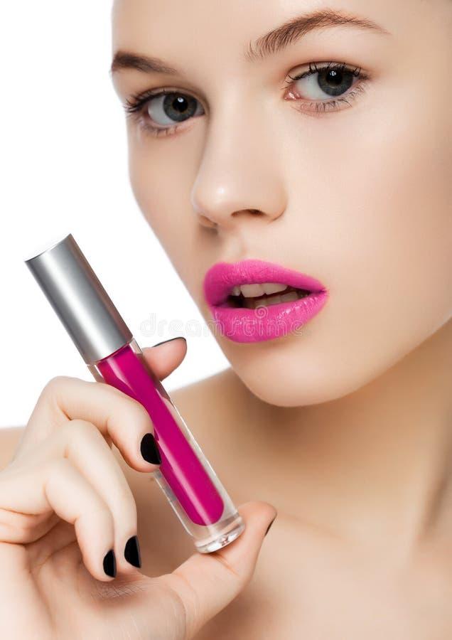 Belle fille tenant le tube violet liquide de rouge à lèvres image libre de droits