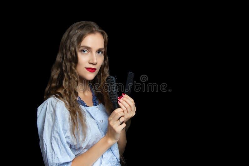 Belle fille tenant les peignes noirs photographie stock libre de droits