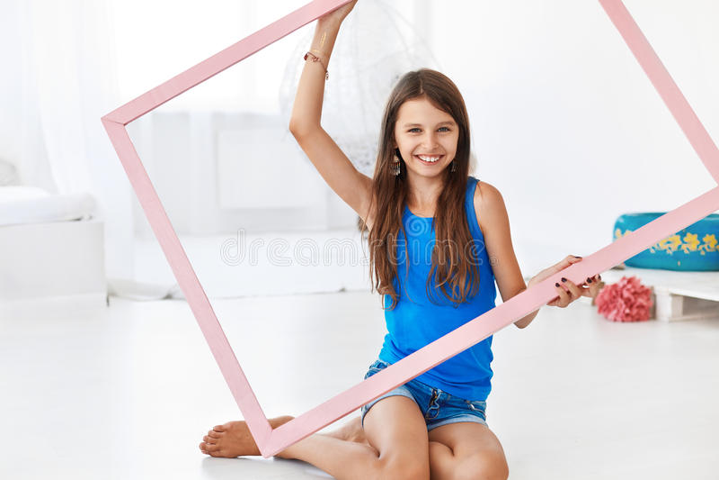 Belle fille tenant un cadre et un sourire images stock