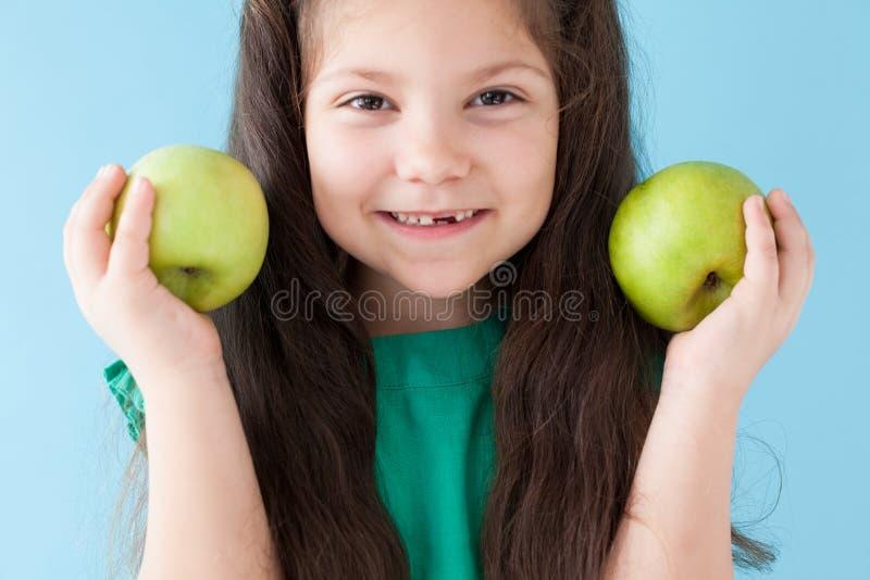 Belle fille tenant un fruit vert d'Apple photos stock