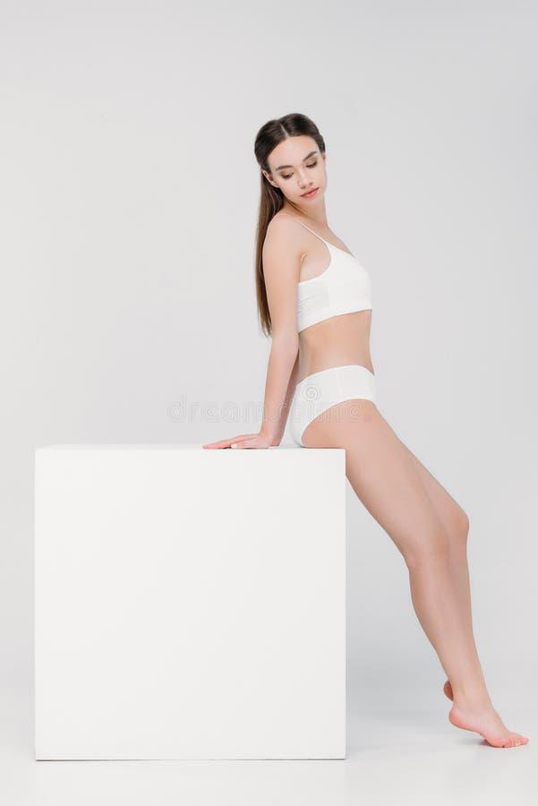 belle fille tendre dans les sous-vêtements posant près du cube blanc photographie stock