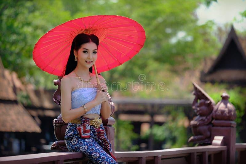 Belle fille thaïlandaise dans le parapluie rouge de costume traditionnel de robe As images stock