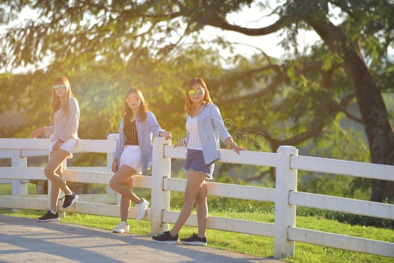 Belle fille trois se tenant sur le ton chaud extérieur de barrière images stock