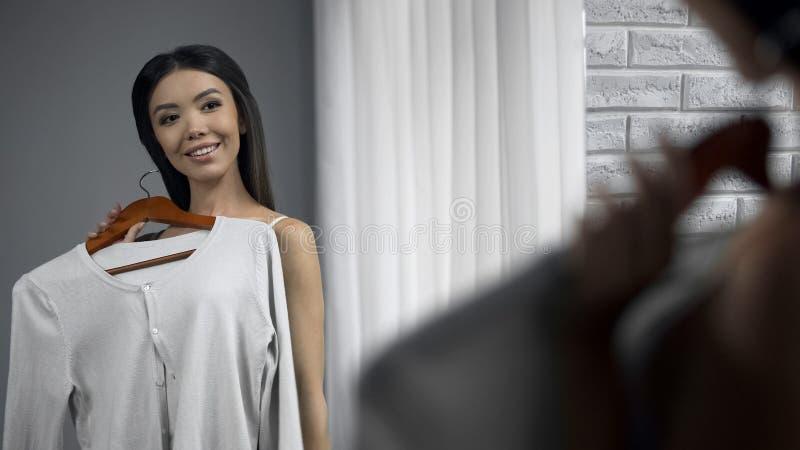 Belle fille vérifiant comment les chemisiers regarde sur elle devant le miroir, vêtements photo libre de droits