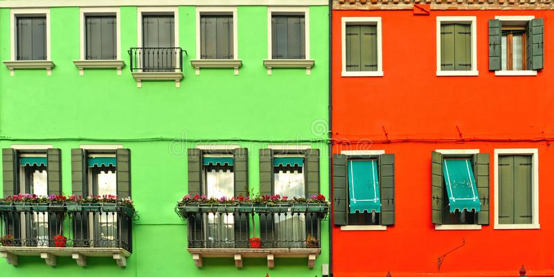 Belle finestre con gli otturatori verdi e balcone con i fiori sulla parete rossa e verde Case variopinte sull'isola di Burano vic fotografia stock