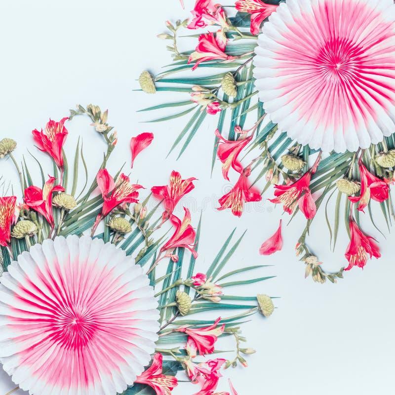 Belle foglie tropicali e fiori esotici con i fan di carta del partito su fondo bianco, vista superiore Copi lo spazio Disposizion immagini stock libere da diritti