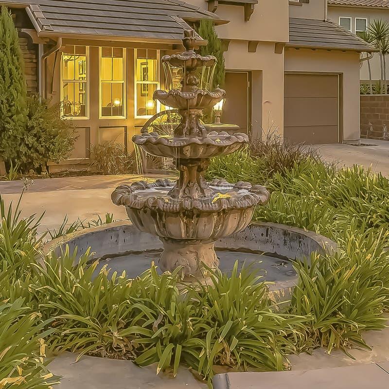 Belle fontaine à gradins de cadre carré au jardin d'une maison contre le ciel avec les nuages gris photo libre de droits