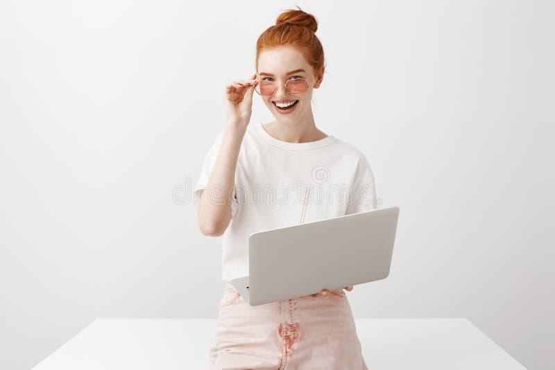 Belle free lance femminili in occhiali da sole alla moda, appoggiandosi tavola, guardando fisso alla macchina fotografica, sorrid fotografia stock libera da diritti