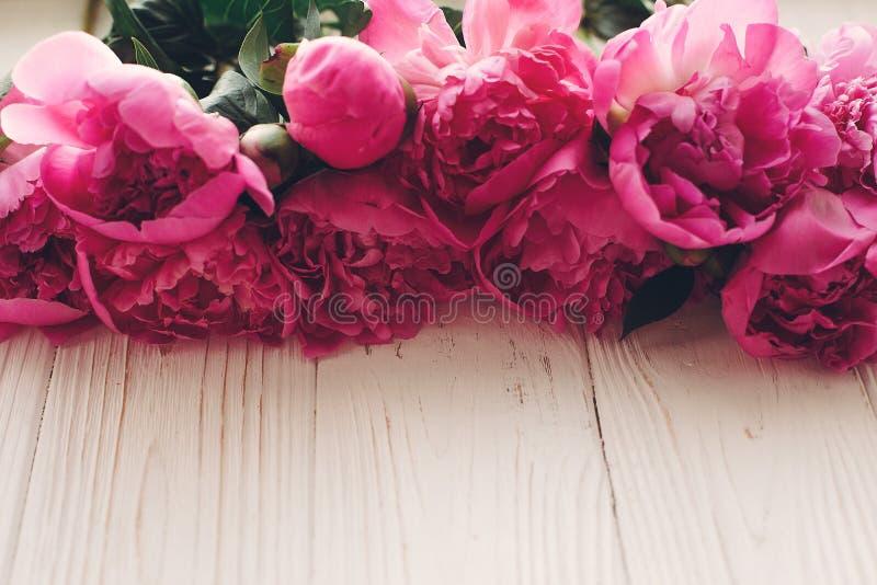 Belle frontière rose de pivoines dans la lumière sur la vue supérieure de fond en bois blanc rustique, l'espace pour le texte maq photographie stock